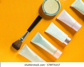 Cosmetics on orange background workplace. Top view