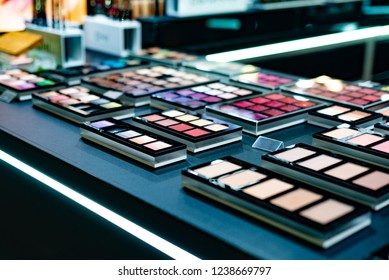 Cosmetics on the shop window with a variety of colors and shades, mascara, powder, paint for beauty and makeup. Consumerism, retail and purchase concept.