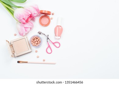 Cosmetics and pink tulips on a white background. Flat view with space for text. The view from the top. The concept of beauty.