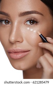 Cosmetics. Portrait Of Sexy Young Woman Applying Concealer On Smooth Soft Facial Skin Under Eyes. Closeup Beautiful Healthy Female Doing Makeup Using Corrector. Beauty Product Concept. High Resolution