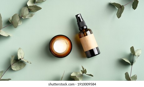 cosmetics products branding mockup. Jar of moisturizer cream and amber glass spray bottle on green background with eucalyptus leaves. Organic herbal beauty products