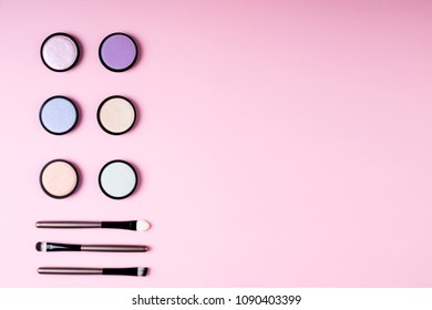 Cosmetics products for makeup eye eyeshadow and accessories on pink background flat lay. Fashion and beauty blogging concept. Top view, copy space