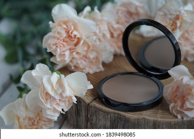 cosmetics sculptor, black jar, against a background of flowers
