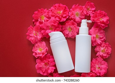 Cosmetics & Skin Care mockup . cream and serum with rose extract in white cosmetic bottles  on pink roses on a red background  . cosmetic mockup. Flat lay, top view, copy space.