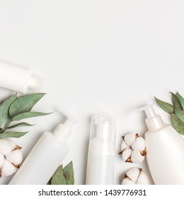 Cosmetics SPA branding mock-up. White cosmetic bottle containers with cotton flowers, eucalyptus twigs on gray background top view flat lay. Natural organic beauty product concept, Minimalism style