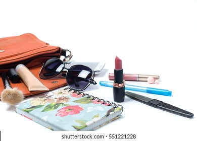 Cosmetics and women's accessories fell out of the orange handbag on wight background.