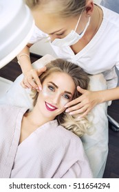 Cosmetologist applaying anti-aging eye gel pads
