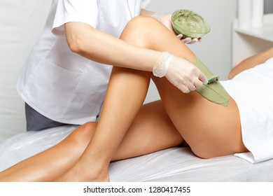 Cosmetologist applies seaweed mud on a  woman's hip in a cosmetological beauty clinic