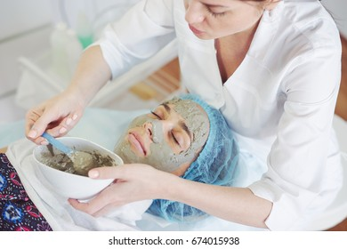 Cosmetologist applying alginate mask to patient face in salon. Top view.