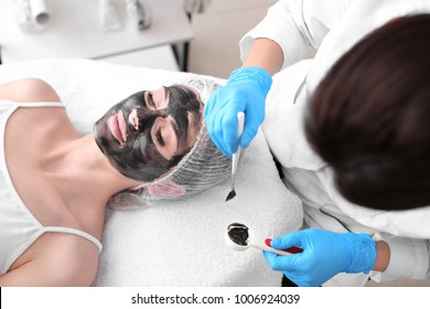 Cosmetologist applying carbon nanogel on woman's face, closeup. Peeling procedure