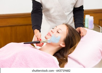 Cosmetologist applying cosmetology mask to young womans face, while she is laying on couch covered with pink towel