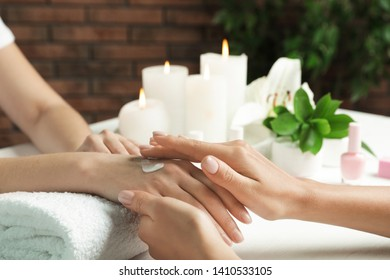 Cosmetologist applying cream on woman's hand at table in spa salon, closeup with space for text