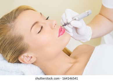 Cosmetologist applying permanent make up on lips