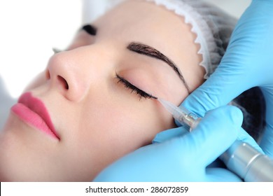 Cosmetologist applying permanent make up on eyes, close-up