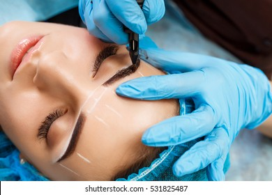 Cosmetologist applying permanent make up on eyebrows- eyebrow tattoo