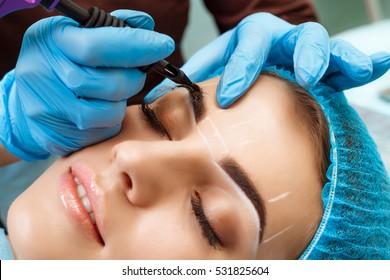 Cosmetologist applying permanent make up on eyebrows- eyebrow tattoo