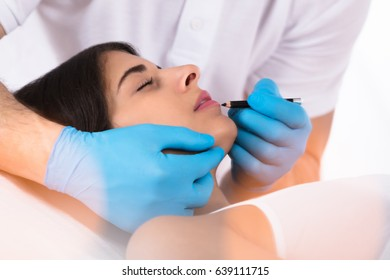 Cosmetologist Applying Permanent Make Up On Woman's Lips Lying On The Bed With Closed Eyes