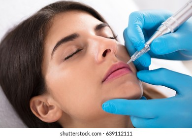 Cosmetologist Applying Permanent Make Up On Woman's Lips In Beauty Spa