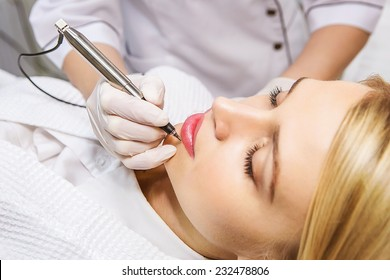 Cosmetologist applying permanent make-up on lips