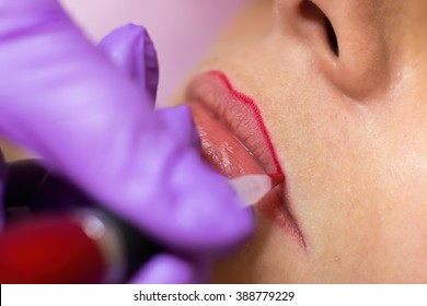 Cosmetologist applying permanent makeup on lips Selective focus and shallow Depth of field