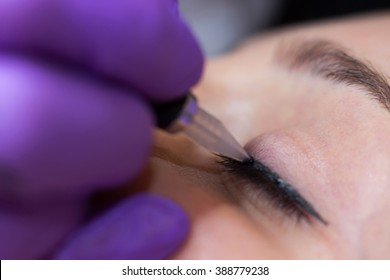 Cosmetologist applying permanent makeup on eyes Selective focus and shallow Depth of field