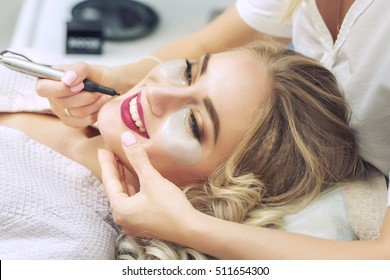 Cosmetologist applying permanent make-up on lips