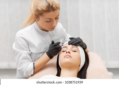 Cosmetologist in black gloves holding syrringe with filler near girl's forehead. Cosmetologist doing beauty procedure for patient. Cosmetological clinic. Healthcare, clinic, cosmetology. Beauty salon