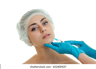 cosmetologist in blue gloves conducts injections on the face of a young girl