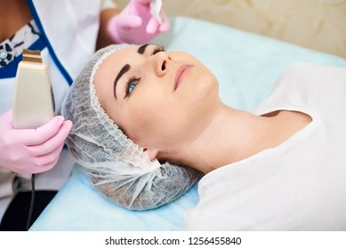 A cosmetologist carries out health procedures on the face of a young girl, skin cleansing, acne treatment