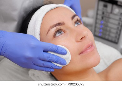 The cosmetologist cleanses with a tonic the face skin of a beautiful, young woman in a beauty salon.Cosmetology skin care.