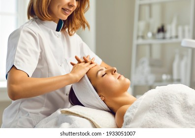 Cosmetologist or dermatologist making facial beauty massage treatment for relaxed young woman face with fingers movements in beauty spa salon. Facial treatment, massage, skincare, cosmetology concept