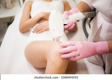The cosmetologist does laser hair removal of the legs