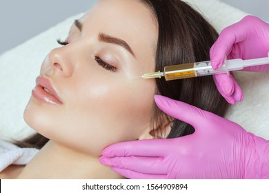 Cosmetologist does prp therapy on the face of a beautiful woman in a beauty salon. There is in vitro  blood plasma, ready for injection. Cosmetology concept.