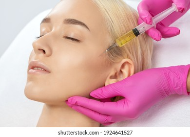 Cosmetologist does prp therapy on the face of a beautiful woman in a beauty salon. Cosmetology and professional skin care.