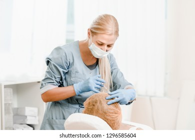 Cosmetologist doing injection of fluid to stimulate hair growth