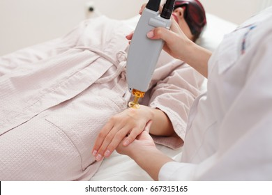 Cosmetologist doing laser epilation to woman's or girl's arm. Spa. Cosmetic procedures. Laser hair removal. Concept of health care, lifestyle and medicine service.