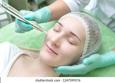 Cosmetologist doing microneedle to a young girl in the beauty salon close up