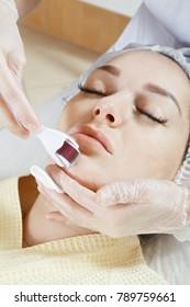 Cosmetologist hands at chin micro needling procedure. Vertical closeup shot