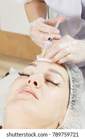 Cosmetologist hands making injection to forehead at plasma needling sking rejuvenation procedure. Vertical closeup shot
