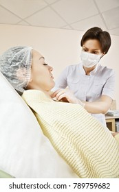 Cosmetologist injecting ozone to chin. Patient is sitting in chair with closed eyes. This therapy is purposed to increase oxygen in a body. Vertical low angle shot