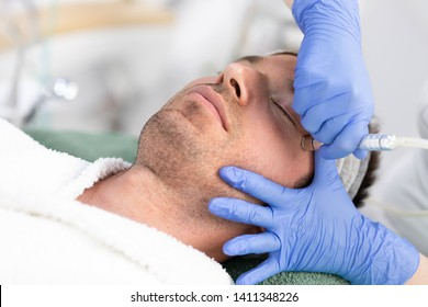 Cosmetologist is lifting laser rejuvenation device under male face at beauty salon