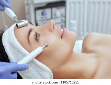 The cosmetologist makes the apparatus a procedure of Microcurrent therapy of a beautiful, young woman in a beauty salon. Cosmetology and professional skin care.