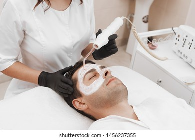 The cosmetologist makes the apparatus a procedure of Microcurrent therapy of a beautiful, man in a beauty salon. Receiving electric darsonval facial massage procedure.