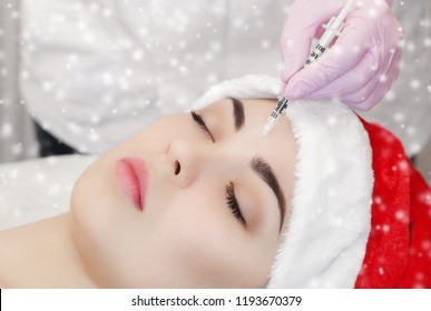 The cosmetologist makes the Botulinum toxin injection on the face skin of a beautiful, young woman in the Santa Claus hat. New Year's and Cosmetology concept