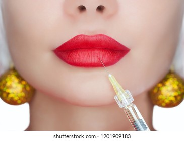 The cosmetologist makes the Botulinum toxin injection on the lips of a beautiful, young woman. New Year's and Cosmetology concept