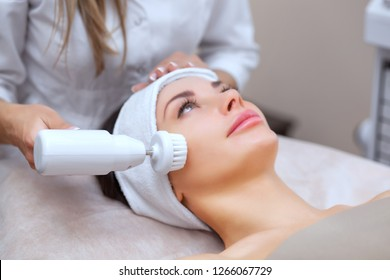 The cosmetologist makes the Hardware face cleaning  procedure with a soft rotating brush of a beautiful, young woman in a beauty salon. Cosmetology and professional skin care.