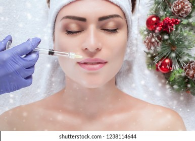 The cosmetologist makes injections in the lips of the patient.  Closeup woman face and new year wreath.