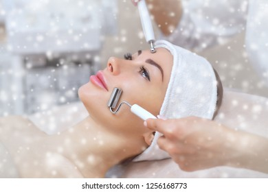 The cosmetologist makes the Microcurrent therapy procedure of a beautiful woman in a beauty salon. Closeup woman face and snowflakes.