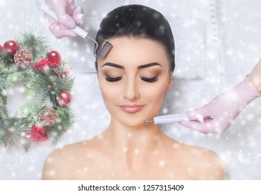 The cosmetologist makes the Microcurrent therapy procedure of a beautiful woman in a beauty salon. Closeup woman face and new year wreath with snowflakes.