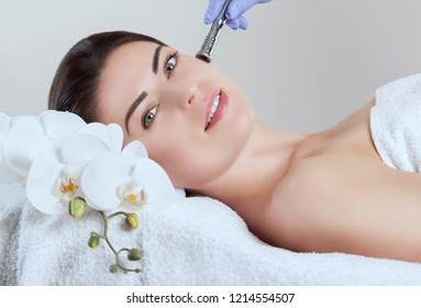 The cosmetologist makes  Microdermabrasion procedure of the facial skin of a beautiful, young woman in a beauty salon.Cosmetology and professional skin care.